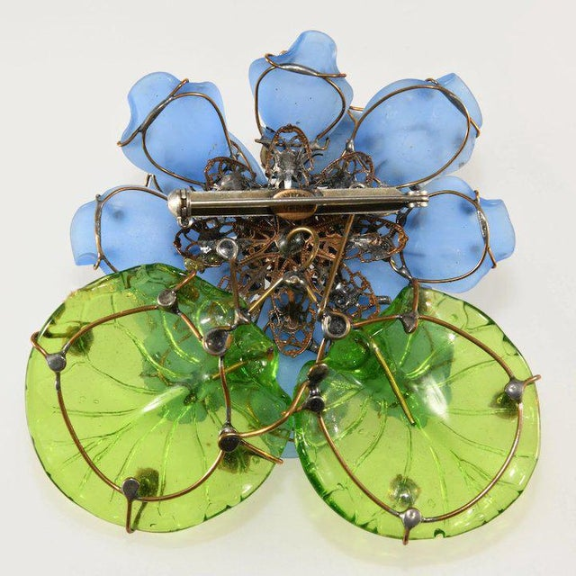 Huge flower brooch made with cornflower blue frosted glass petals and bright green molded glass leaves. Rhinestones in two...