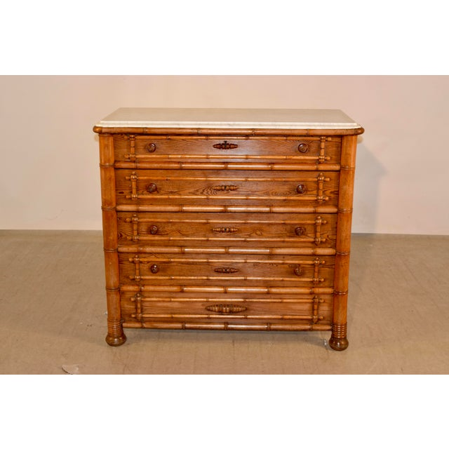 19th century faux bamboo pine and cherry chest of drawers from France. The top is made from Carrara marble and has a...
