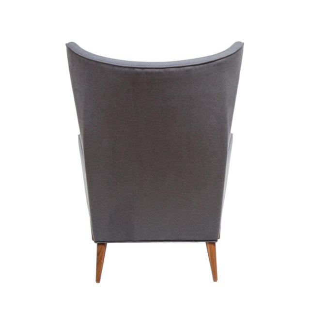 Sculpted high back armchair. The chair is detailed with single loose down feather seat cushion on solid turned legs. Seat...