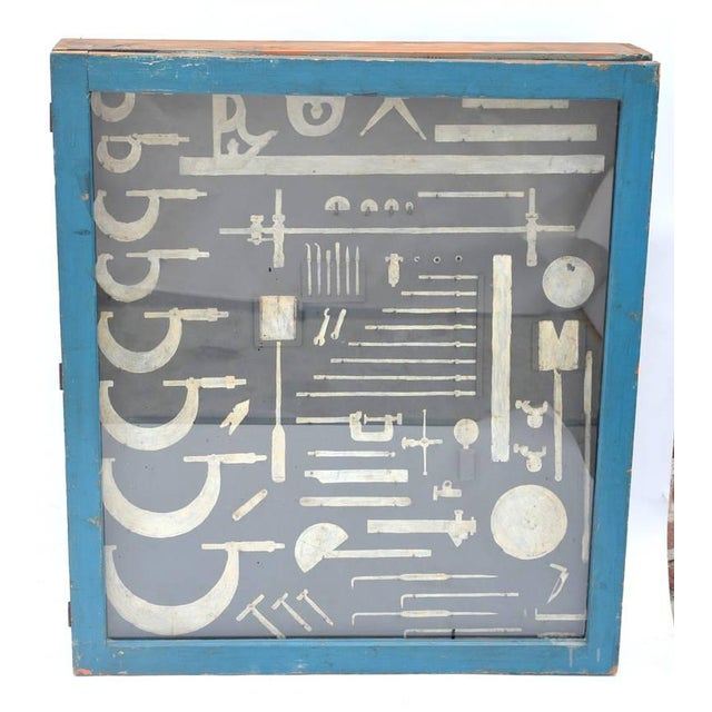 Unique carpenters tool cabinet, closed with a glass door and hand painted tool shaped with hooks. Can be used as a display...