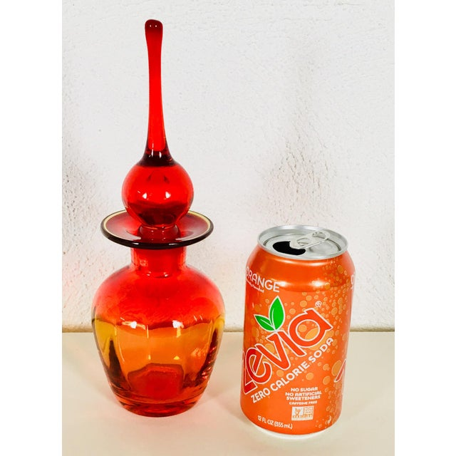 This is a Blenko hand blown glass jar with a finial stopper, made with a brilliant red and orange amberina color pattern ....