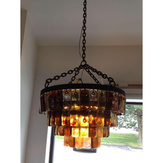 Four tiers of beautiful handblown glass tiles. by Feders; Five lights to interior. Heavy wrought iron chain and frame.