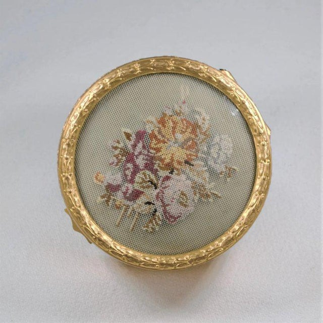 This is beautiful gilt metal box featuring a petit point floral spray under a convex glass top. A charming collector's...