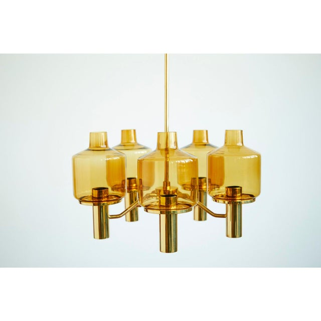 Stunning Brass and Glass Chandelier by Hans-Agne Jakobsson, featuring five lanterns in a smokey yellow shade. Made by the...