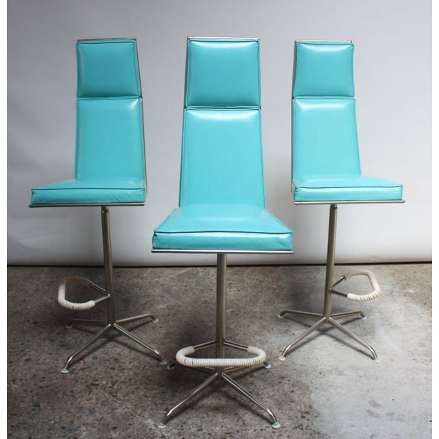 Set of three swivelling barstools composed of turquoise vinyl and brushed aluminium frames with cord-wrapped footrests....