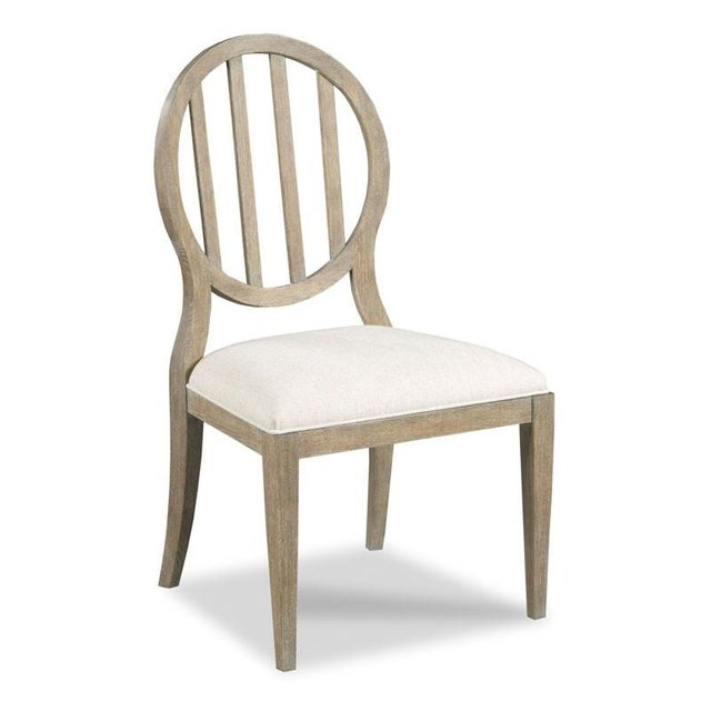 A graceful oval back is accented with a colonnade of shaped slats above an upholstered seat raised by gradual tapering...