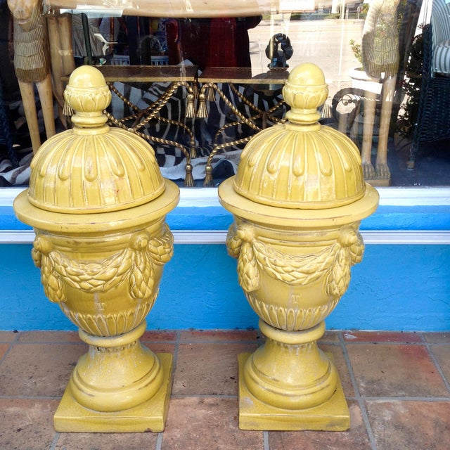 Dramatic in scale and color. The urns are fashioned with removable tops and adorned with swags. Each has an incised letter...