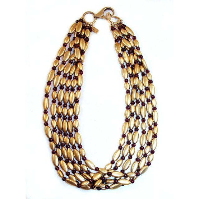 Stunning Nini Ricci multi-strand gold-plated sterling oval bead necklace interspersed with round garnet beads. This lovely...