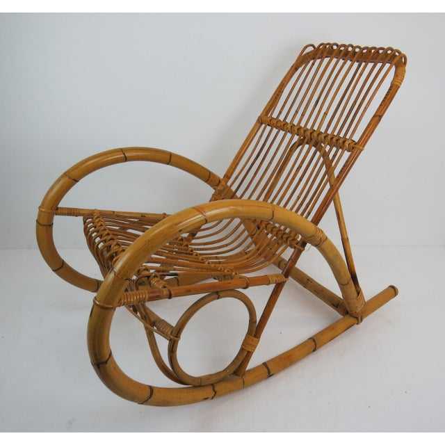 A rare Franco Albini style bamboo and rattan rocking chair that features a steam bent bamboo frame. This rocking chair was...
