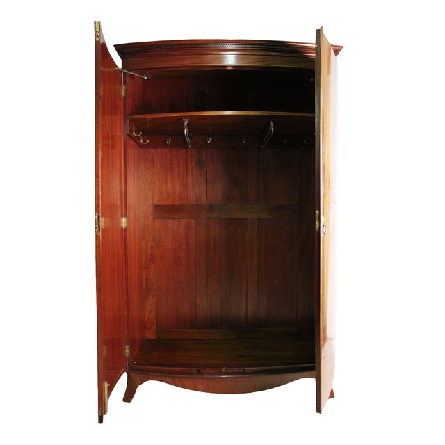 A rare, full door English Hepplewhite-style mahogany armoire with flamed mahogany oval inlays. Interior fitted with...