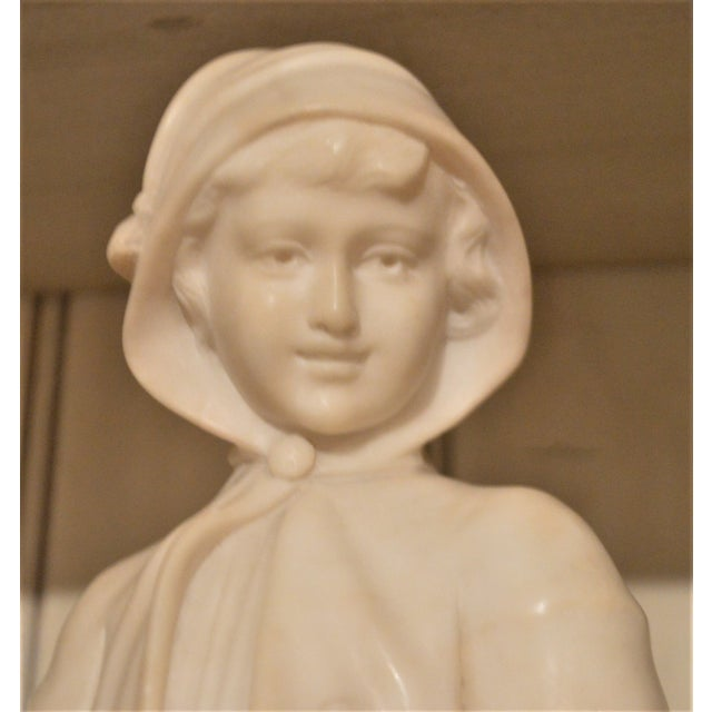 Charming small marble bust of a pretty young girl wearing a cape. The marble bust is sitting on a sickle, made in Italy,...