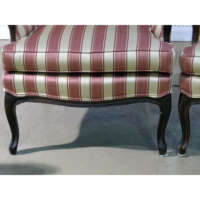 Pair of Mid 20th Century Louis XV style wingback chairs with striped upholstery.