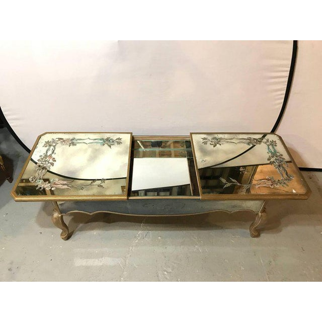 An Italian Reverse Paint Decorated Sliding Top Coffee Low Table. The gilt gold design legs and mirrored apron support a...