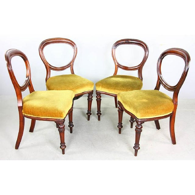Set of four (4) Victorian Style Balloon Back Mahogany Dining Chairs from the 20th Century. Chairs feature rounded open...