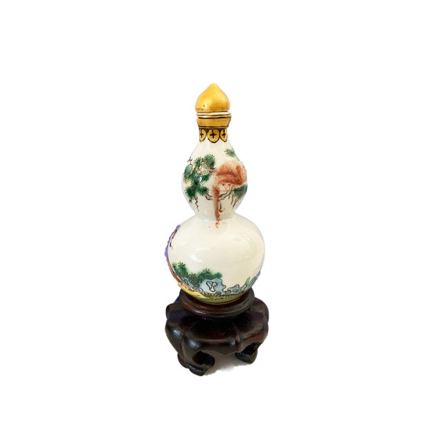 Super hand painted chinoiserie Famille rose porcelain snuff bottle depicting a figure/tree etc.. marked on the bottom with...