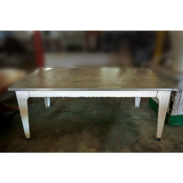 Long contemporary industrial style table with off white iron base and metal top. Very sturdy, great for many uses,...
