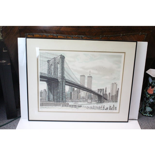 """Pre-9/11 New York City print, titled, """"Hail Brooklyn Bridge"""" in shades of blue and gray. On white mat, glass, and black..."""