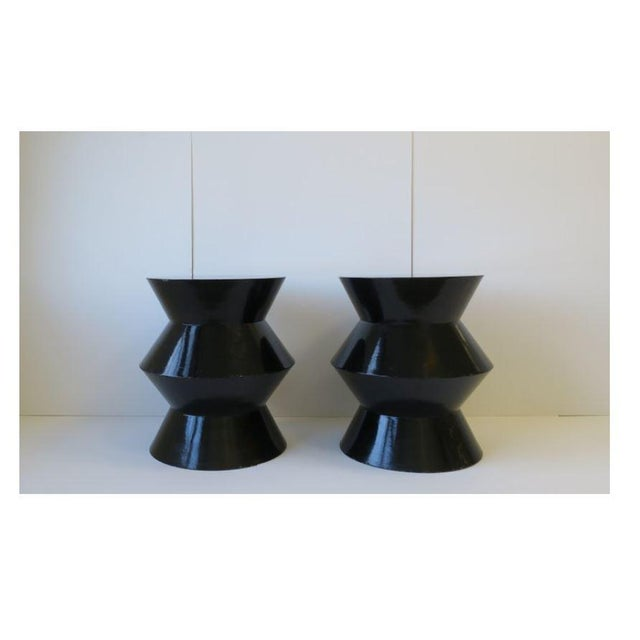 A chic pair of round black lacquer end, side, or drink tables. Postmodern. Made in the late 20th century. Table style also...