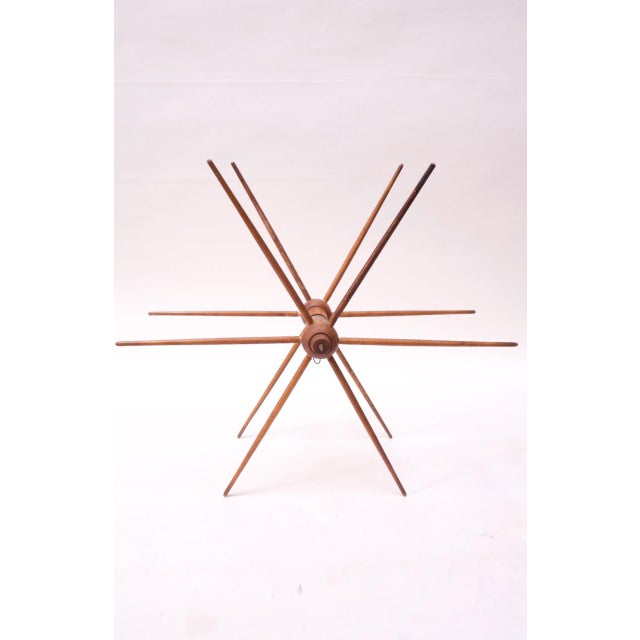 Circa 1940s silk winder from a textile mill with twelve spokes and a small strip of leather around the center shaft....
