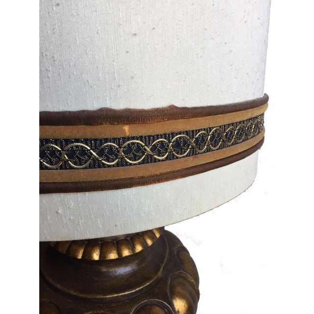 This stunning table lamp features a gilded finish and it's original vintage shade. In working condition, it brightens any...
