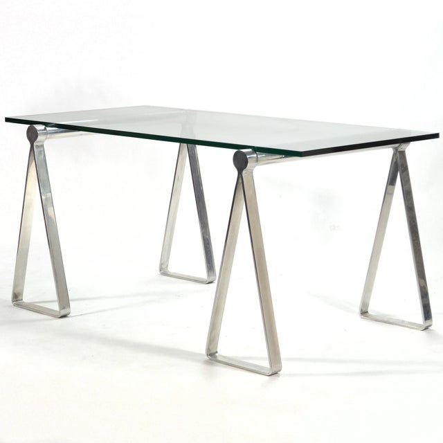 An ingenious and attractive design. Two Campaign-style aluminum sawhorse forms support a glass top creating a wonderful...