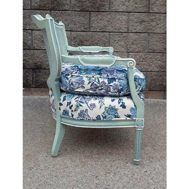 A French cane back settee with a loose blue floral seat cushion. The frame has a aqua blue antiqued painted finish. This...