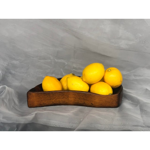Hand carved from a single piece of wood, this modern bowl has an organic shape and be used as a small fruit bowl on a...