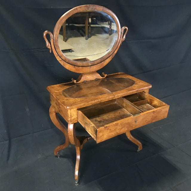 Beautiful French dressing table with mirror in carved walnut with elegant swan neck support uprights. On the sides the...