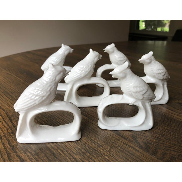 A collection of six ceramic napkin rings. These porcelain white decorative pieces are topped with perching birds resting...