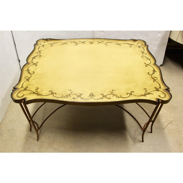 Lovely tray top coffee table. Tray is wood and features scalloped edges and a decorative painted finish. The base is a...