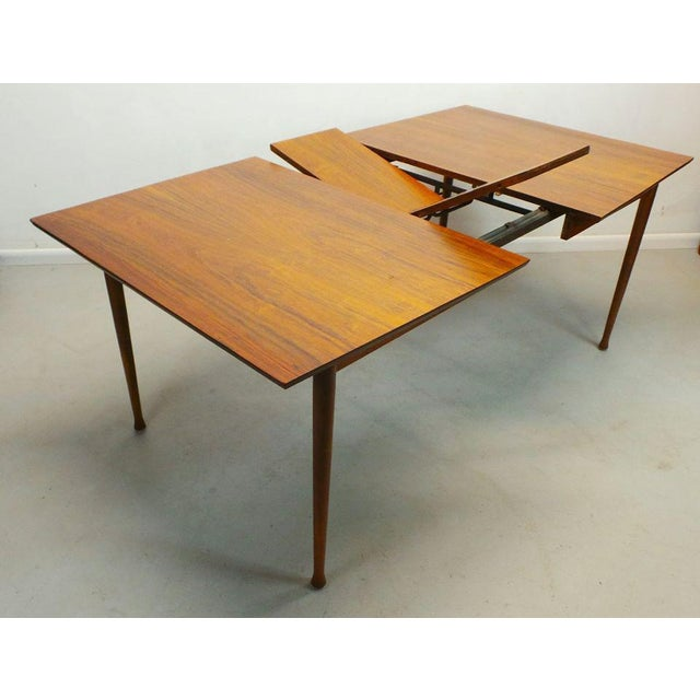 Mid century modern walnut & rosewood expanding dining table with butterfly leaf by Frank and Son. This gorgeous walnut...