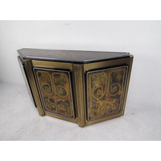 This unique Mid-Century cabinet features an artistic acid-etched floral designs on it's unique brass finish. Center door...