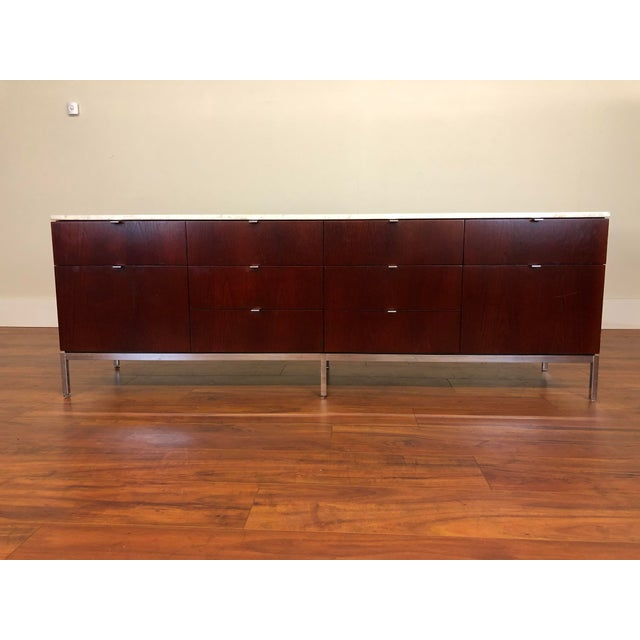 Florence Knoll four position credenza made by Knoll Associates. It appears to be either walnut or teak with an off white...