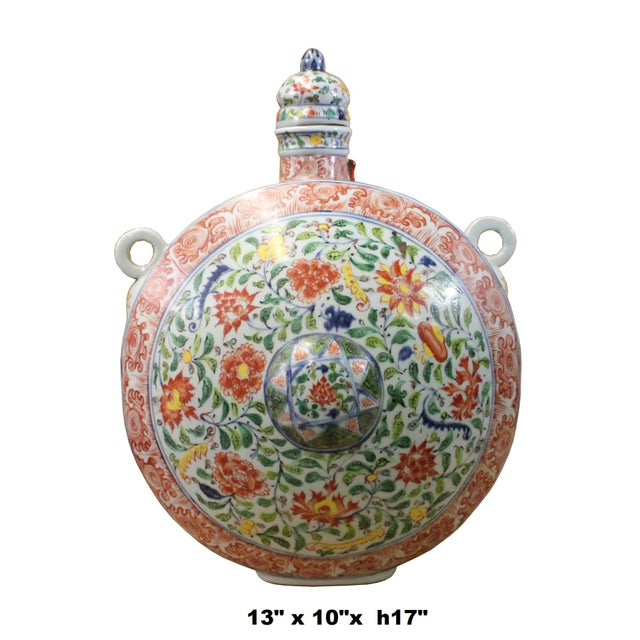 This is a handmade oriental porcelain pot jar in BaoYue shape in white base and multi-color flowers graphics ( mainly...