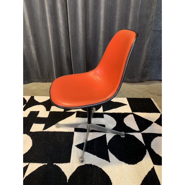 Bold and iconic Eames chair manufactured by Herman Miller in 1972, as marked on bottom. Poppy red trimmed in black...