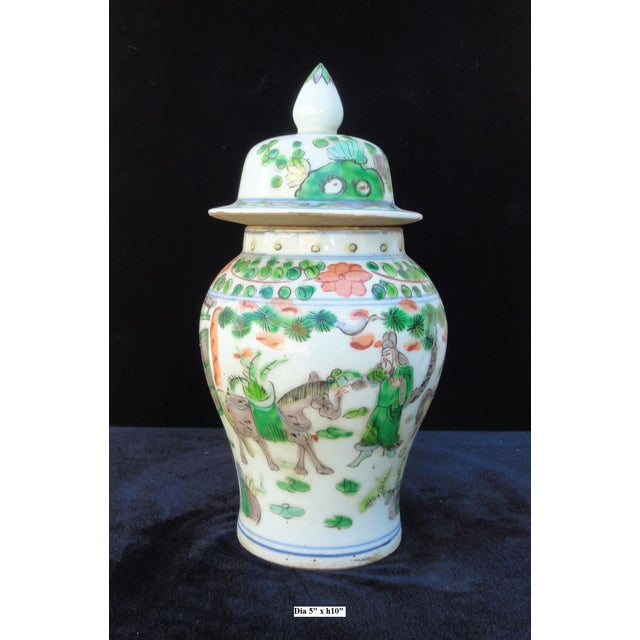 "Small ginger jar in white base color with oriental people scenery on the body. Dimensions: Dia 5""x h10"" Origin: China..."