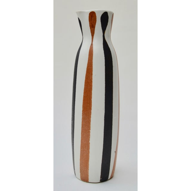 A 1950s elegant and simple tall studio pitcher by master potter Frank Mann of Vermont. His simple bold style with black...