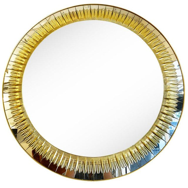 Large round Mid-Century mirror by Cristal Art with gold decorative engraving. The edge is brass and the frame wood.