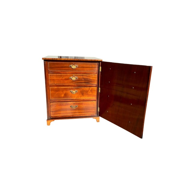 With a rectangular top over a door constructed to look like drawers with wood knobs, the door opening to expose a later...