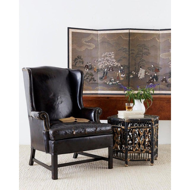Stately English George III style wingback armchair finished in black leather hides. The wing chair features fully...