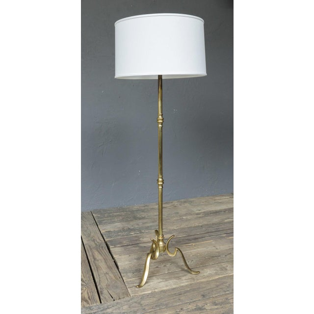 Solid brass floor lamp with tripod base composed of three curved and cast legs supporting a stem with turned components....