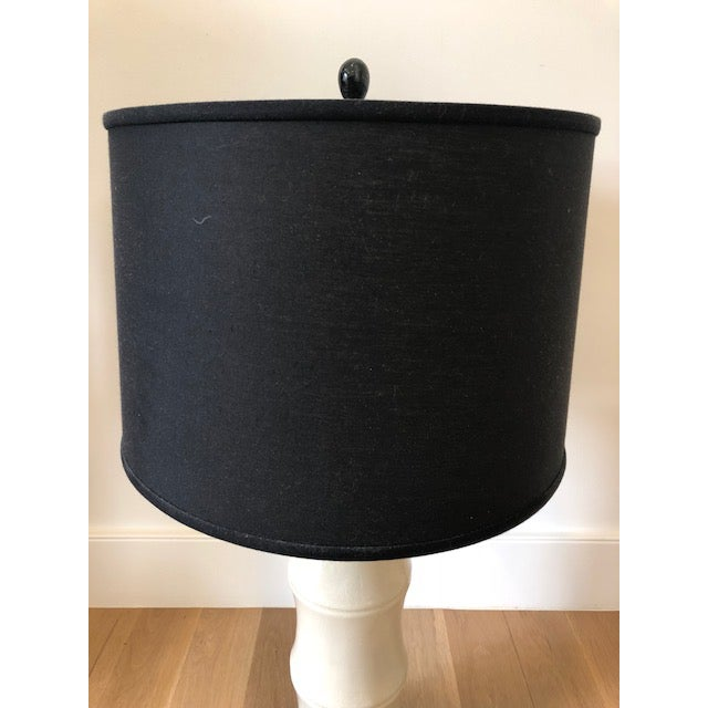 Cream crackle glaze table lamp with a black linen tapered drum shade and black marble finial. The shape of the lamp mimics...