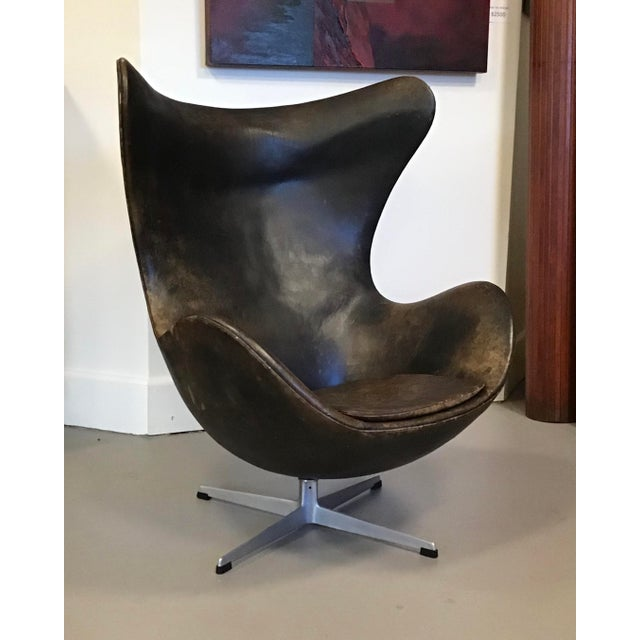 An Early Arne Jacobsen for Fritz Hansen Egg Chair in brown leather with aluminum swivel base. The Egg Chair is one of the...