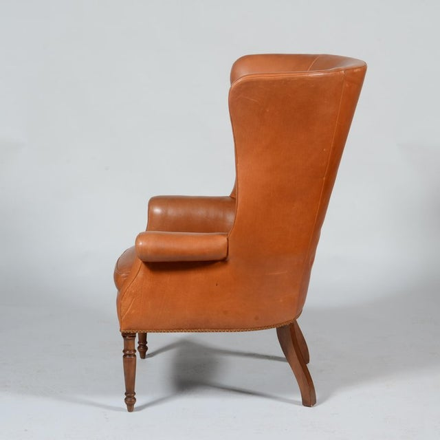 A classic pair of saddle leather high back wing back chairs that feature exaggerated proportions and a perfect amount of...