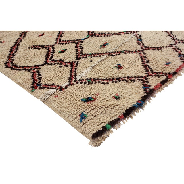 Vintage hand-knotted Moroccan wool rug featuring an abstract and asymmetrical pattern of Berber designs in an assortment...