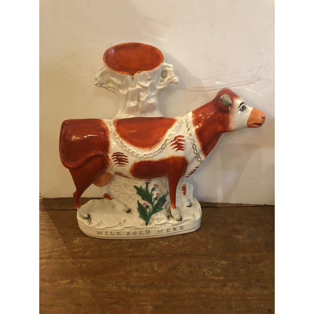 A wonderful rare very large pair of Staffordshire spill vases having orange and cream colored cows.