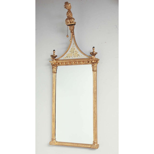 A pair of American Federal small scale gilt wood pier mirrors, each with pineapple finial above distinctive eglomise...