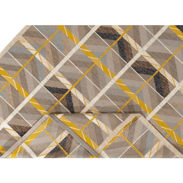 A 21st century Modern Scandinavian-style flatweave rug with a beige field and yellow accents in an allover geometric...