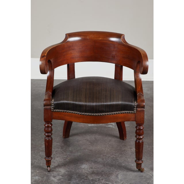 A handsome pair of Swedish mahogany armchairs, with concave back, inscrolled arms and turned front legs, circa 1850. Seats...
