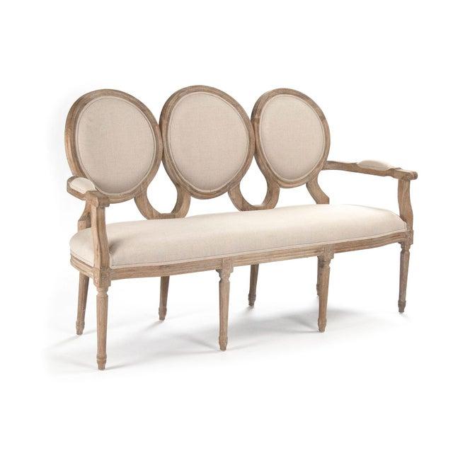Settee upholstered in natural linen, padded arms on limed grey oak frame.